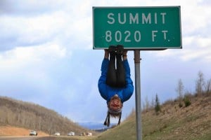 Rob Greenfield hangs from a summit elevation sign. Photo by Brent Martin