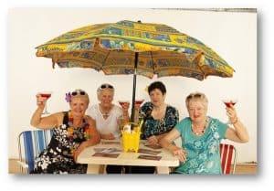 A group of older women enjoy drinks under a beach umbrella