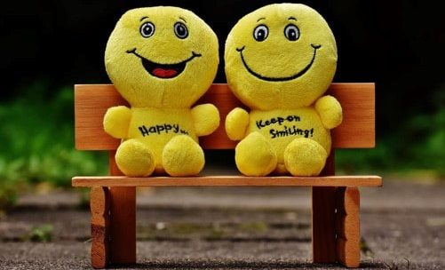 Image of two cartoonish puppets on a bench
